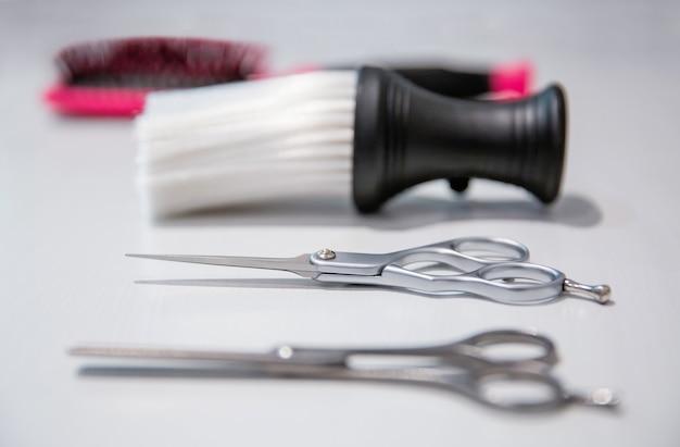 Крупный план парикмахерского оборудования на белом фоне деревянных. селективный акцент на ножницы.