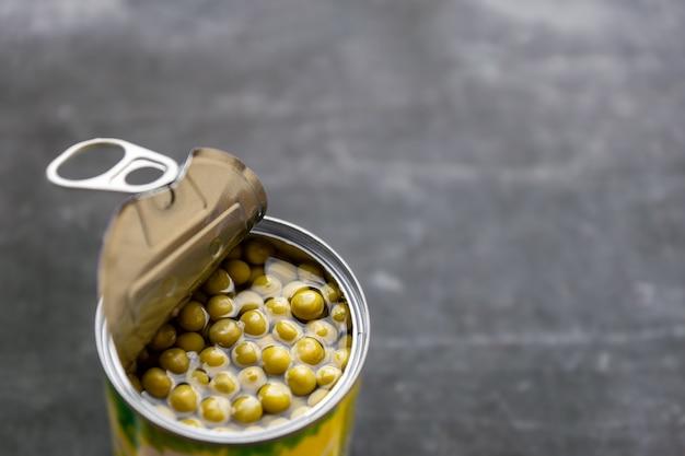 硬い自然光と灰色の表面を持つ半分開いたエンドウ豆の缶詰缶のクローズアップ