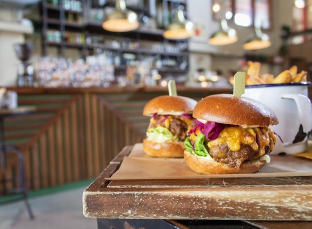 背景をぼかした写真の木製トレイ上のハンバーガーのクローズアップ