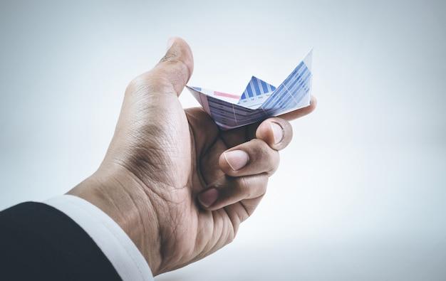 Крупным планом руки бизнесмена, держащего лодку бумажный граф