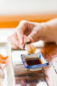 Крупным планом руки девушки окунают кусок суши с креветками в соевый соус с васаби