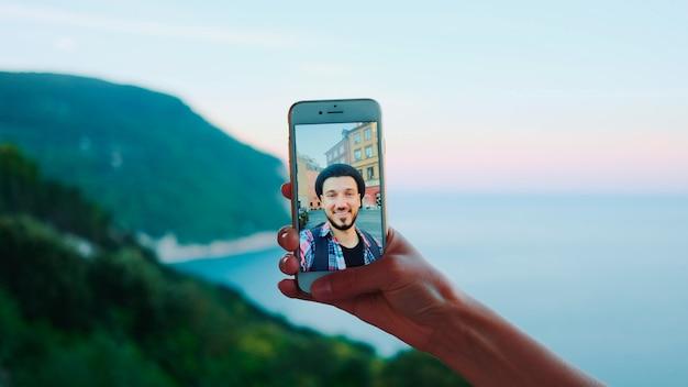 海の美しい風景の前で男とビデオ通話中にスマートフォンを持っている手のクローズアップ...