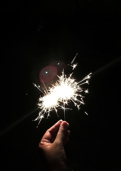 Closeup of hand holding sparkler with black background