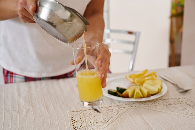 柑橘類のプレスから透明なガラスに絞りたてのオレンジジュースを注ぐ女性の手のクローズアップ。朝食の準備
