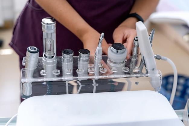현대적인 필링 장비를 들고 있는 전문 여성 미용사의 손을 클로즈업. 미세 박피술. 현대 피부 관리 및 치료 기술.