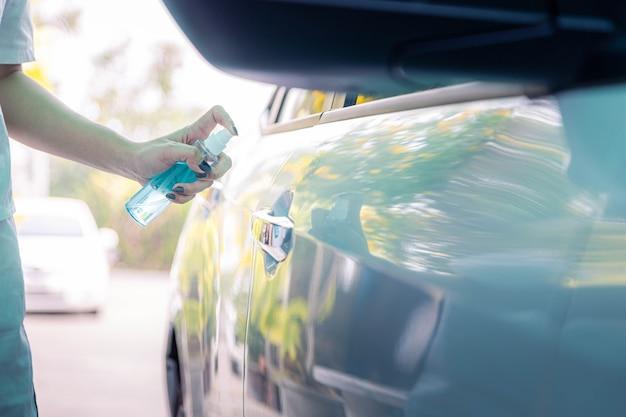 여자의 손을 닫고 자동차 문 손잡이에 알코올, 소독제 스프레이를 뿌리고 있습니다. 세균 코비드-19 바이러스와 개인 위생 개념의 오염.