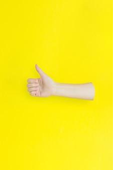 黄色の背景に対して親指を立てるサインを示す手のクローズアップ。