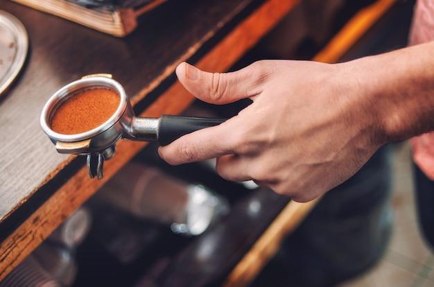 挽きたてのコーヒーとバリスタホルダーと手のクローズアップ。ソフトフォーカス