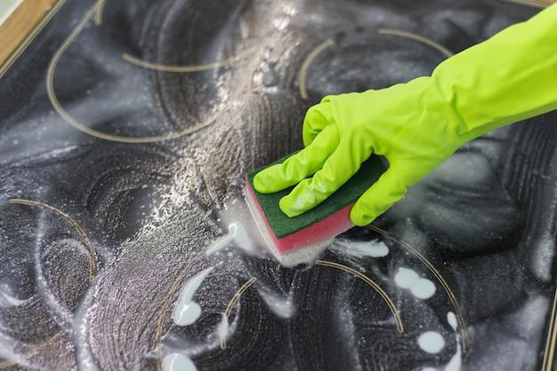 スポンジと洗剤で現代の調理ガラスセラミック電気表面を掃除する手の女性のクローズアップ