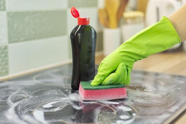 スポンジと洗剤でモダンな調理用ガラスセラミック電気表面を掃除する手の女性のクローズアップ