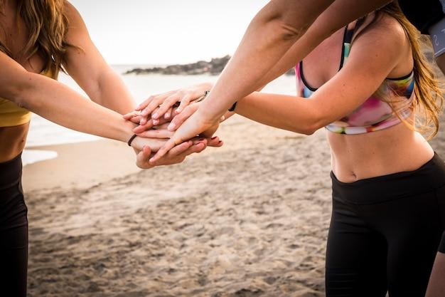 健康を維持し、健康的なライフ スタイルを楽しむためのフィットネス運動をしている 3 人の美しい若い女の子の手と体のクローズ アップ