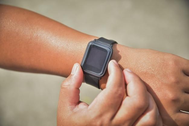 スマートウォッチ画面、アクティブなスポーツ活動のスマートウォッチタッチボタンとタッチスクリーンで手と手首のクローズアップ