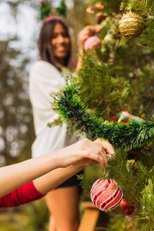Крупный план рук, украшающих елку. друзья украшают елку на открытом воздухе. рождество и открытый концепт.