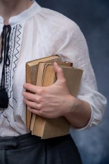 Крупным планом руки, держащие стопку книг концепция образования