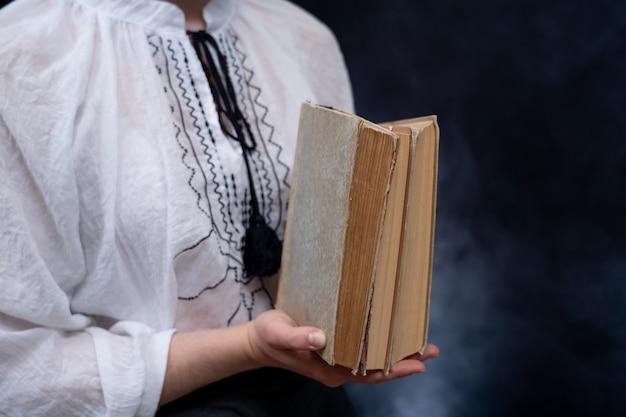 Крупным планом руки, держа стопку книг