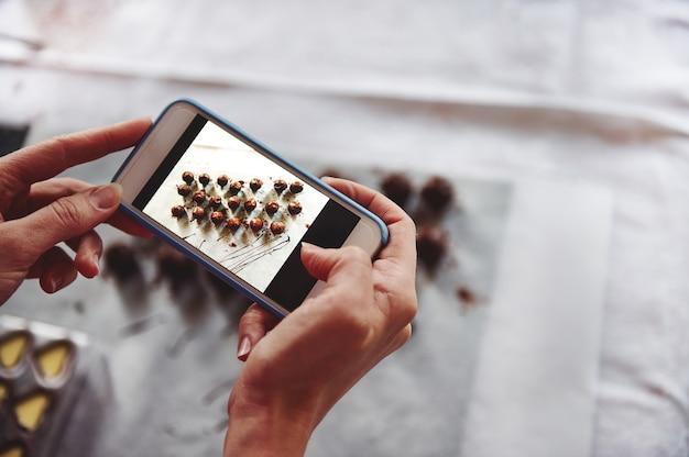 携帯電話を持って白いテーブルクロスでおいしいチョコレートプラリネの写真を撮る手のクローズアップ。ライブビュー体制の携帯電話。閉じる
