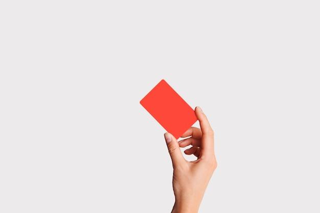 プラスチック製のクレジットカードを持っている手のクローズアップ