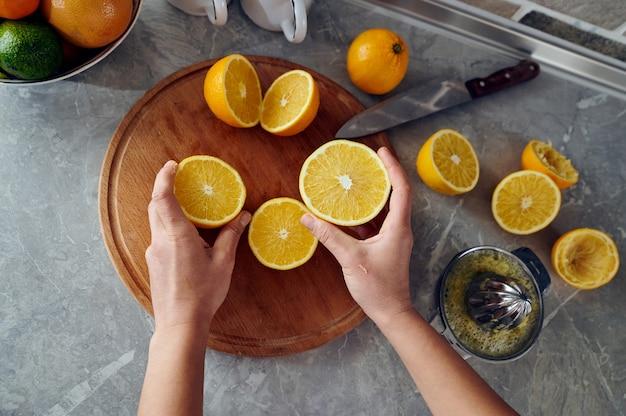 Крупным планом руки женщины, держащей половинки апельсинов на деревянной кухонной доске