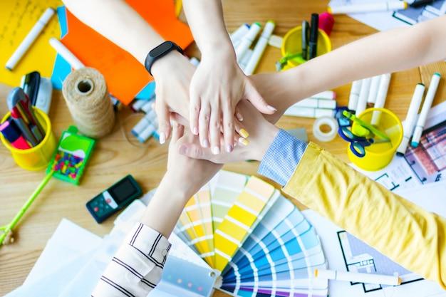 クリエイティブ・オフィスの机の上に互いの上に手を繋いでいるビジネス人々の手のクローズアップ。色見本、部屋のレイアウトのあるテーブルにいる建築家やインテリアデザイナー。チームワークの概念。