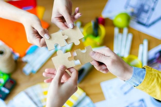 クリエイティブ・オフィスの机の上にパズルを置くビジネス人々の手のクローズアップ。色見本、部屋のレイアウト、事務用品のテーブルにいる建築家やインテリアデザイナー。チームワークの概念。