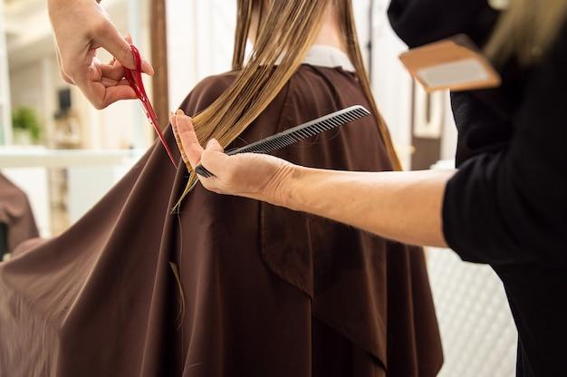 美容院で長いブロンドの髪を切る美容師の手のクローズアップ