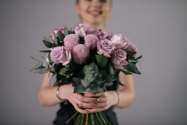 흰색 배경에 꽃다발을 들고 웃는 여자 꽃집의 손의 근접 촬영