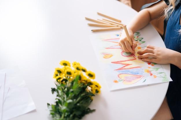 Крупный план рук до неузнаваемости девушки, рисующей цветными карандашами за столом