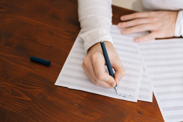 Крупный план рук до неузнаваемости человека, пишущего музыкальные ноты карандашом на нотах