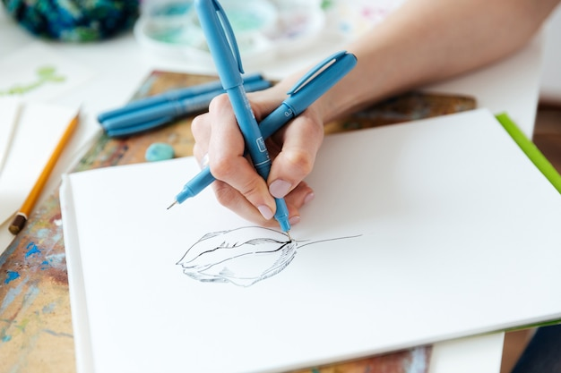ゲルインクペンで描く女性アーティストの手のクローズアップaytテーブル