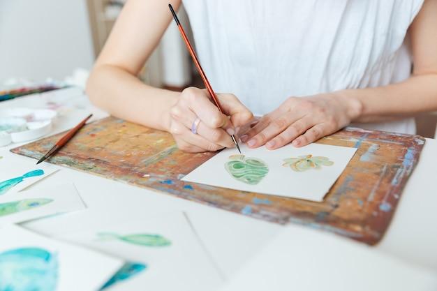 Крупный план рук женщины-художника, рисующего кистью и акварельными красками на столе