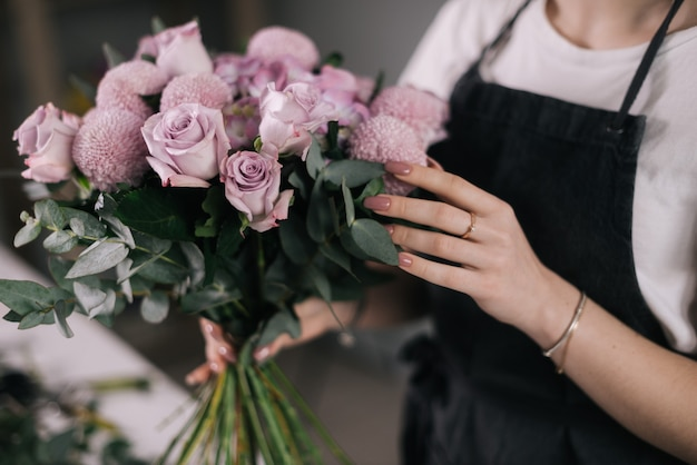 흰색 바탕에 꽃다발을 들고 있는 여성 꽃집의 손 클로즈업