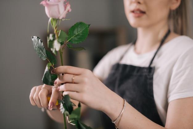 흰색 배경에 있는 테이블에서 신선한 장미를 깎는 앞치마를 입은 여성 꽃집의 손을 클로즈업