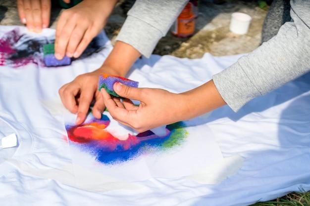 Крупным планом руки рисуют на футболке снаружи