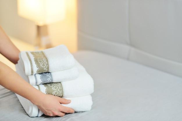 침대 시트에 신선한 흰 수건 더미를 넣어 손의 근접 촬영. 룸 서비스 청소 호텔 방.