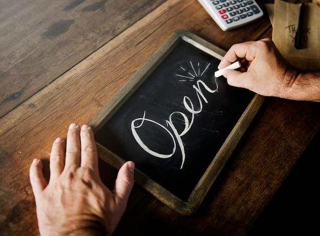 Макрофотография руки, писать открытое слово на доске