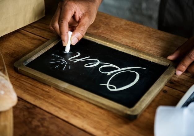 Крупным планом руки, написание открытого слова на доске