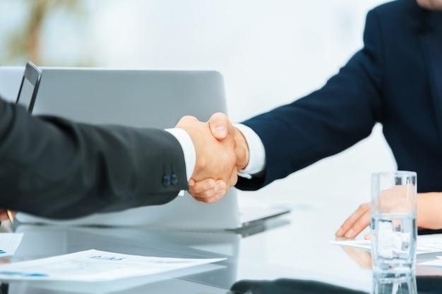Крупным планом рукопожатие деловых партнеров на фоне рабочего места