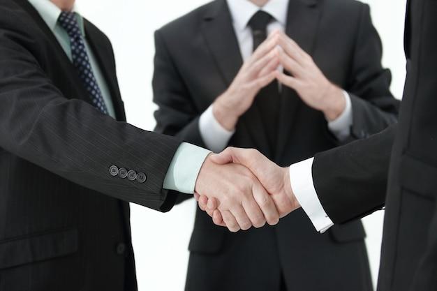 ボケ味の背景に対して撮影されたビジネススーツを着ている2人の起業家の握手のクローズアップ