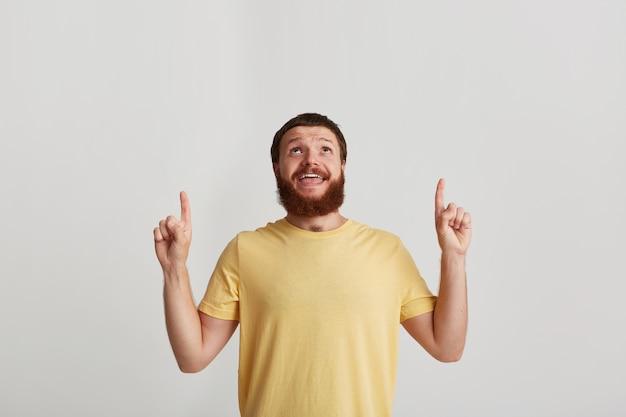 수염을 가진 행복한 잔인한 젊은이의 근접 촬영은 t 셔츠를 입는다.
