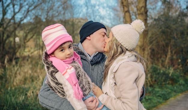 숲 위에 키스 하는 그녀의 작은 딸과 함께 행복 한 커플의 근접 촬영.