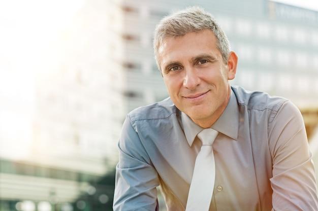 Крупным планом счастливый зрелый бизнесмен улыбается открытый