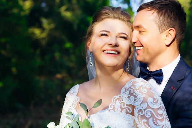 お互いの腕と甘い笑顔で幸せな新婚夫婦のクローズアップ