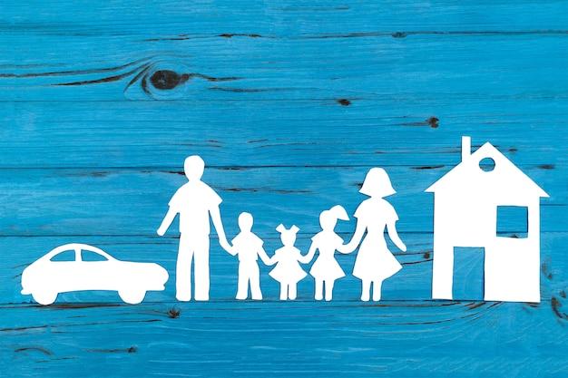 青の背景に幸せな紙家族のクローズアップ