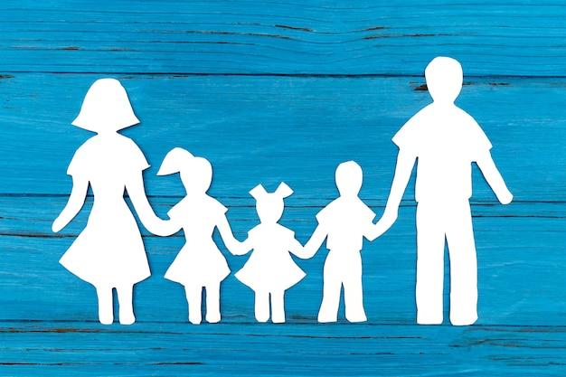 青い表面に幸せな紙家族のクローズアップ