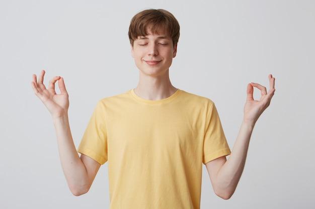 目を閉じて幸せで平和な若い男のクローズアップは黄色のtシャツを着て落ち着いて瞑想を白い壁に隔離された感じ