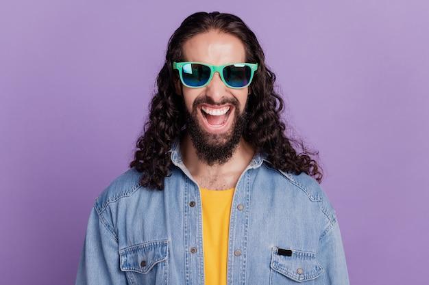 Крупным планом счастливый улыбающийся парень, смотрящий на камеру, носит летние солнцезащитные очки с открытым ртом