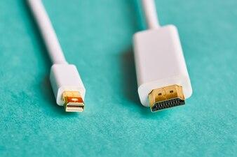 青色の背景にHDMIとミニディスプレイポートケーブルのクローズアップ
