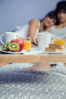 Крупным планом здоровый завтрак подается на деревянный поднос, готовый к употреблению, и счастливая пара в любви обниматься. концепция здорового питания и домашнего образа жизни.