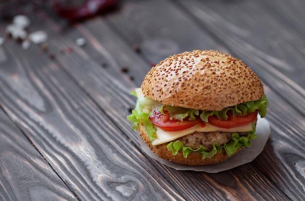 Крупный план самодельных бургеров говядины с салатом и майонезом служил на маленькой деревянной доске. темный фон