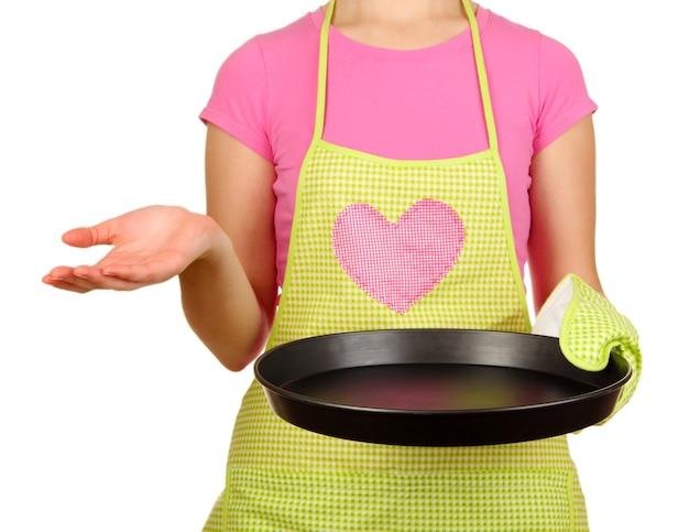 Крупный план домохозяйки в фартуке, держащей сковороду, изолированную на белом